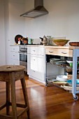 Rustic wooden stool, modern kitchen counter, crockery on trolley with drawers, white drawer units and stainless steel cooker under extractor fan