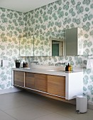 Long washstand with wooden sliding doors below mirrored wall units on wall with floral wallpaper