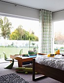 Corner of room with glass walls, partially visible bed and classic, green children's chairs around model boat on play table