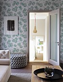 Wohnzimmer mit teilweise sichtbarem Couchtisch aus Holz und Sofa, dahinter schwarzweiss gemusterter Pouf an floral gemusterter Tapete an Wand, Blick durch offene Tür in tiefergelegte Nebenräume