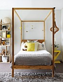 Four-poster bed with scatter cushions and mobile hanging from wooden frame next to modern wooden shelves of soft toys in teenager's bedroom with grey carpet and rug