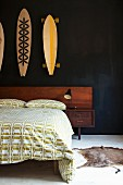 Double bed with wooden headboard and green and white bed linen with pattern of cars below painted skateboards hung on black wall