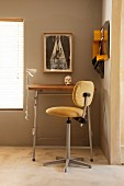 Tall stool with upholstered seat and backrest in front of high desk against sand-coloured wall with closed louver blind on window