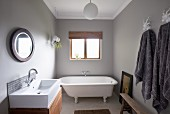 Free-standing vintage bathtub below window, modern washstand with wooden base cabinet opposite grey towels on hooks in bathroom painted pale grey