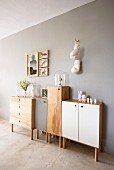 Half-height, wooden console cabinets, some with coloured doors, against wall painted pale grey