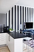 Open-plan kitchen with black worksurface on breakfast bar and bar stools; TV on sideboard against elegant, black and white striped wallpaper in background