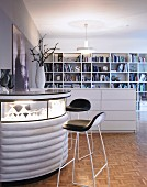 Bar stool at semicircular bar with illuminated glass top next to half-height, white chest of drawers used as partition in front of bookcase