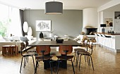 Classic wooden chairs at large dining table below pendant lamp; lounge area next to window in background opposite open-plan kitchen