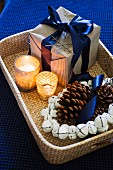 Wrapped Christmas present, tealights, wreath of bells and pine cones on wicker tray
