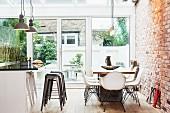 Moderner Essplatz und Mittelblock mit Barhockern in offener Küche mit Sichtmauerwerk Terrassentür