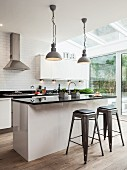 Retro bar stools at island counter in designer kitchen with white, glossy cupboard fronts