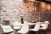 weiße Schalenstühle an Esstisch und schlichte Hängeleuchten vor Ziegelwand