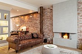 Open-plan interior with old leather sofa next to open fire; concrete chimney breast flanked by brick walls