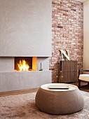 Runder Couchtisch vor offenem Kaminfeuer und Beton Vorsatzschale an Ziegelwand