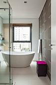 Violetter Deckel als Farbkleks in elegant modernem weißem Bad mit freistehender Wanne und dynamischem Wandmuster