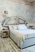 White, antique bedroom with marbled walls, worn wooden floor and reclaimed wooden elements used as bed headboard