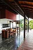 Frameless, sliding glass elements form transition between roofed wooden terrace and contemporary, open-plan kitchen with integrated dining area
