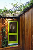 Front door with green frame and glass panels in modern, wooden house with climbers supported on trellising