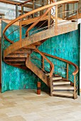 Curved staircase in corten steel with wooden treads in front of curved wall of verdigris copper panels