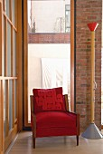 Red armchair with wooden frame next to modern standard lamp in corner of room with floor-to-ceiling window