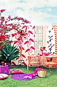 Different flamingo print patterns, outdoor furniture and accessories in shades of red and purple; woman standing on stool hanging up fairy lights