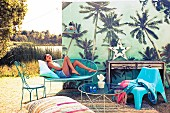Dekoration für Outdoor-Party mit einem Mix azurblauer Sitzmöbel, Teppich und Sitzkissen vor Palmenkulisse; junge Frau posiert liegend auf Sitzbank