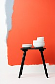 Stacks of white china crockery on black stool against white wall painted with fields of red and grey