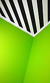Grass green walls abutting ceiling painted with black and white diagonal stripes in corner