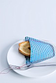 Slice of bread in hand-sewn decorative pocket in checked fabric
