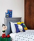 Action figure on side table next to single bed with wooden headboard painted grey in teenager's bedroom