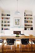 Esstisch und Designerstühle vor offenem Kamin zwischen Bücherregalen in restauriertem Wohnraum mit Stuckdecke