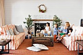 Australian family celebrating Christmas - striped sofa set and coffee table in front of open fireplace with Christmas decorations