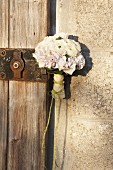 Posy of white flowers on vintage latch of wooden door