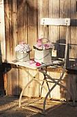 Festive flower arrangements in small zinc buckets on weathered, vintage garden chair against wooden wall