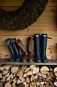 Pairs of boots on board shelf above stacked firewood