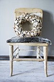 Decorative wreath on old chair with fur seat cushions
