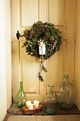 Festive wreath on vintage interior door and collection of glass bottles on floor in door niche
