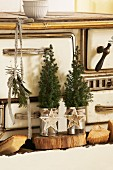 Small fir trees in tin cans decorated with Christmas baubles on wooden board in front of vintage kitchen cooker
