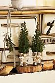Tannenbäumchen in Metalldosen mit Weihnachtsdeko verziert auf Holzbrett vor Vintage Küchenherd