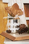Decorated tin can and fir sprigs on open book