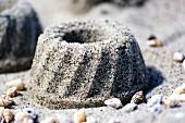 Bundt cake made of sand and seashells on beach