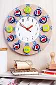 Round wall clock decorated with brightly painted bottle caps and washi tape