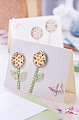 Bottle tops pressed flat and covered with stickers as flowers with paper stems and paper butterfly on elegant white greetings card