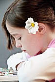 Girl reading with white cosmos flower in hair