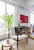 60s-style armchair with wooden frame and wooden side table in loft-style interior front of French windows with view of small potted tree