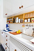 60s-style kitchen with white-painted base and wall units, wooden handles, white-painted worksurface and wooden crockery shelf on wall