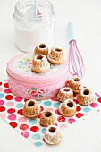 Miniature bundt cakes and pink cake tin on polka-dot napkin
