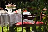 Romantisch gedeckter Kaffee-Gartentisch mit weißer Tischdecke und gepolsterten Holzstühlen mit nostalgischen Flair