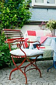 Vintage garden chair on cobbled terrace and comfortable bench with patchwork blanket