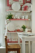 Sales room with white, country-style china displayed on shelves decorated with red and white gingham fabric